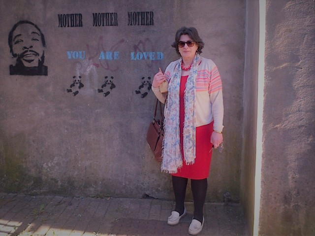 Woman standing beside graffiti art on wall reading 'Mother, mother, mother, you are loved''