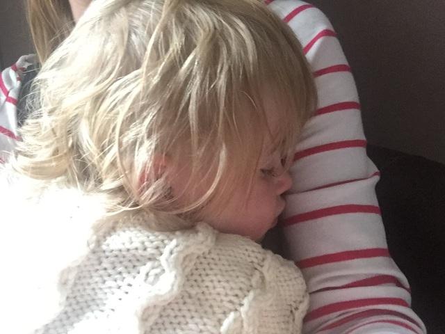 Child asleep on adult's lap